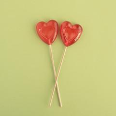 Two Lollipops in heart shape on green background