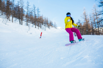 Photo of female athlete wearing helmet and mask snowboarding from snowy slope with trees