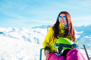 Picture of sports long-haired brunette with helmet resting on chair in winter resort