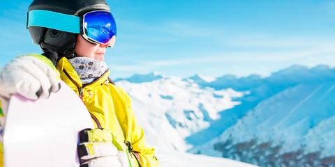 Panoramic photo of smiling woman in helmet and mask with snowboard on background of snowy hills