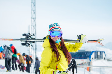 Image of smiling sports woman with skis on her shoulder