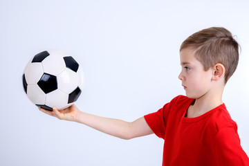 boy in red shirt with soccer ball