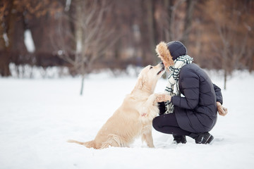 Picture of girl in black jacket with labrador at snowy park