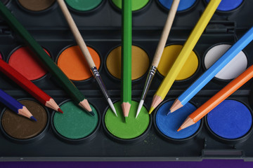 Accessories for creativity, paints, brushes and pencils close-up.
