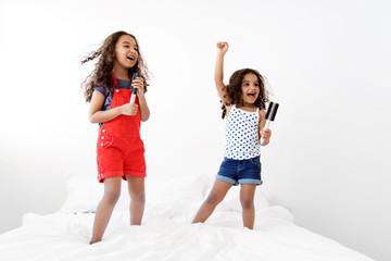 Little girls dancing on bed pretending to be pop stars