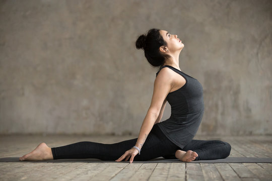 Young woman practicing yoga, doing Single Pigeon, Eka Pada Raja Kapotasana exercise, One Legged King Pigeon pose, working out, wearing sportswear, indoor full length, gray wall in yoga studio