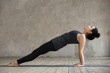 Young sporty woman practicing yoga, doing Purvottanasana exercise, Upward Plank pose, working out, wearing sportswear, black pants and top, indoor full length, gray wall in yoga studio