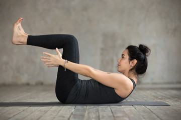 Young sporty woman practicing yoga, doing navasana exercise, boat pose, working out, wearing sportswear, black pants and top, indoor full length, against gray wall in yoga studio
