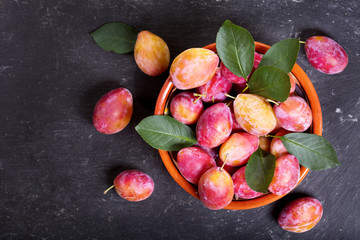 fresh plums with leaves in a bowl