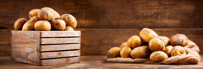 fresh raw potatoes in a wooden box