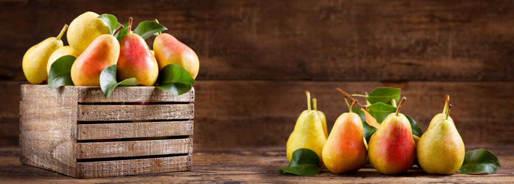 fresh pears with leaves in a wooden box