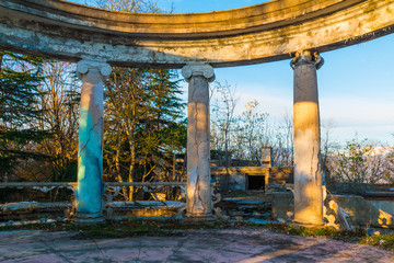 Colonnade of the abandoned building of the former restaurant on the top of Mount Akhun in sunny autumn day, Sochi, Russia