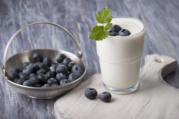 Yogurt with fresh blueberries in a glass on a white cutting board