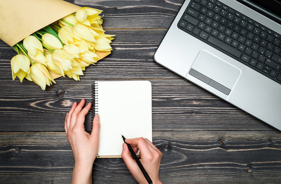 Business woman hands writing in notebook with open laptop computer and bouquet of yellow tulips, copy space. Womens day, March 8, Mothers Day, Easter. Business concept. Flat lay, top view