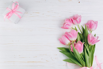 Pink tulips and gift on a white wooden background, copy space and flat lay. Mother's Day concept.