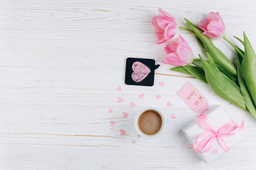 Pink tulips, gift, cup of coffee and paper hearts on a white wooden background, copy space and flat lay. Mother's Day concept.