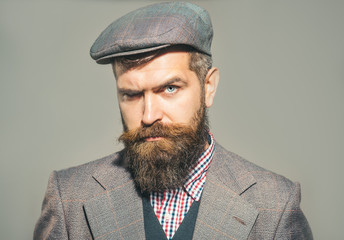 Elegant fashion man with beard and mustache with retro style. Confident man dressed in stylish retro clothes. Pensive man in retro clothes and hat. Vintage fashion - man in suit, shirt, waistcoat, cap
