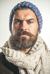 Confident bearded man wearing hat, scarf, leather jacket. Autumn-winter fashion. Perfect style.Brutal caucasian hipster with beard and moustache, stylish man wrapped in scarf.