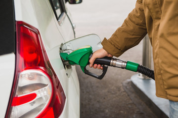 Self-service gas station. A man takes a refueling nozzle