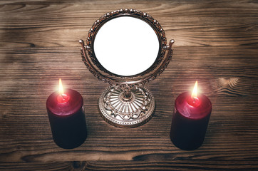 Golden mirror (photo frame) with copy space on the magic table between a two burning candles on both side on wooden desk table background. Future reading.