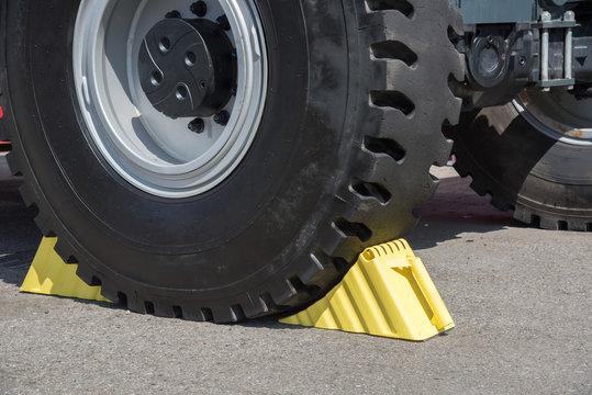 Yellow wheel chocks under the big truck wheels