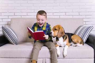 funny boy reading a book with a dog on the couch