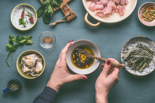 Female hands making marinate for chicken meat meal on kitchen table background with ingredients in bowls , top view. Dieting cooking eating and healthy food concept