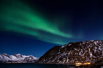 The northern lights over the mountains and the ocean in Grotfjord, Northern Norway