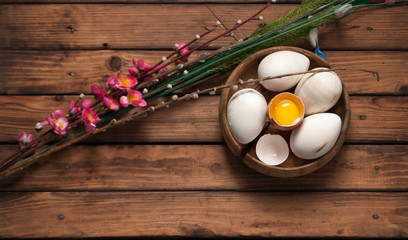 Easter background, eggs and willow branch on wooden background,