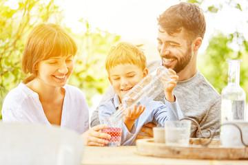 Sohn gießt Eltern Wasser in Glas ein