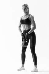 Shot of young muscular female bodybuilder doing heavy kettlebell exercise for deltoids Caucasian fitness model working out with kettlebell on white background in black sportswear