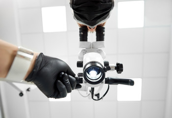 Upwardview of a male dentist wearing black rubber gloves looking in the microscope with the help of professional dental equipment in a white bright dentist office.