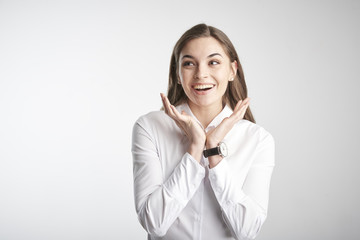 Portrait of happy young businesswoman wearing white shirt while standing with her arms rasied and wondering. Isolated on white background.