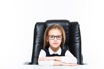 Little girl sitting on the desk at her workplace dressed as a businesswoman