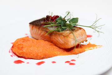 Salmon steak with pumpkin puree, berry sauce and herbs