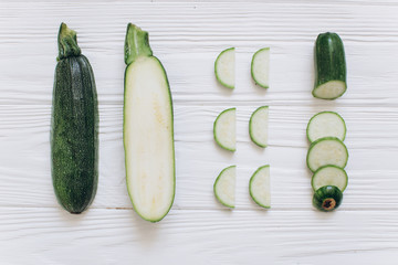 Zucchini is shredded on the white wooden background, top view.