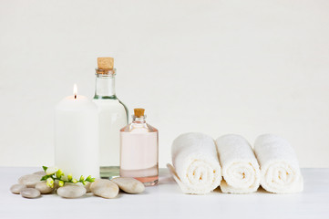 Spa soft light composition with burning candle, terry towels, glass bottles and stones