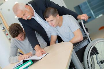 senior teacher helping student in wheelchair