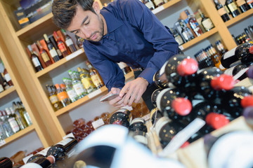 confident young man working at liquor store
