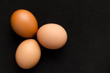 Three brown, chicken eggs black background.