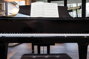 Grand black piano with music sheet
