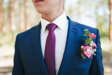 Groom's boutonniere of pink and red roses on a blue suit