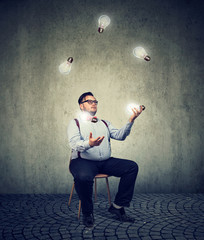 Man fiddling with ideas light bulbs