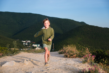 Six year old boy running on a mountain road at sunset with town view. Cool summer evening. Front view.