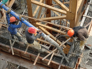 Construction workers pouring wet concrete using concrete spider hose into floor slab form work at the construction site.