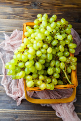 Picture from above of green grapes in wooden box with pink cloth