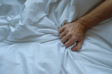 Caucasian man hand grasping on bed
