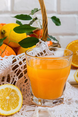 Orange juice in a glass beaker and citrus slices on a white background with copy space