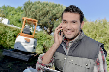 Man outdoors on telephone, digger in background