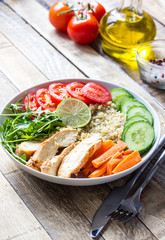 Healthy salad bowl with quinoa, tomatoes, chicken, cucumber, lime and arugula